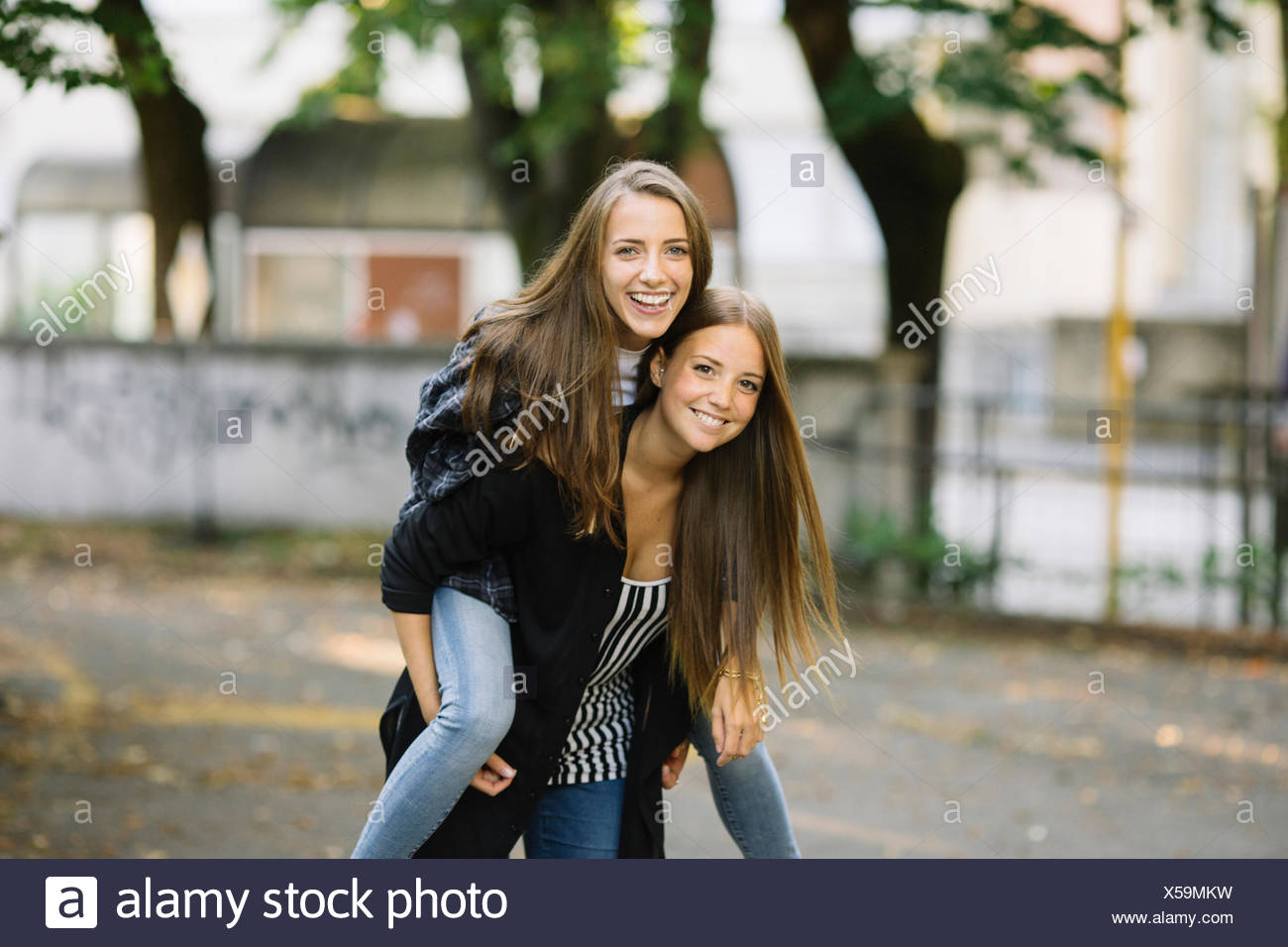 Portrait of young woman giving best friend a piggy back in park - Stock Image