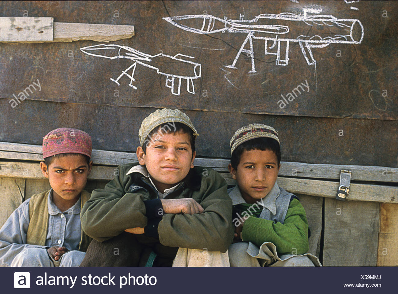 Three Afghan refugee boys sit in front of a chalk drawing of an RPG. - Stock Image