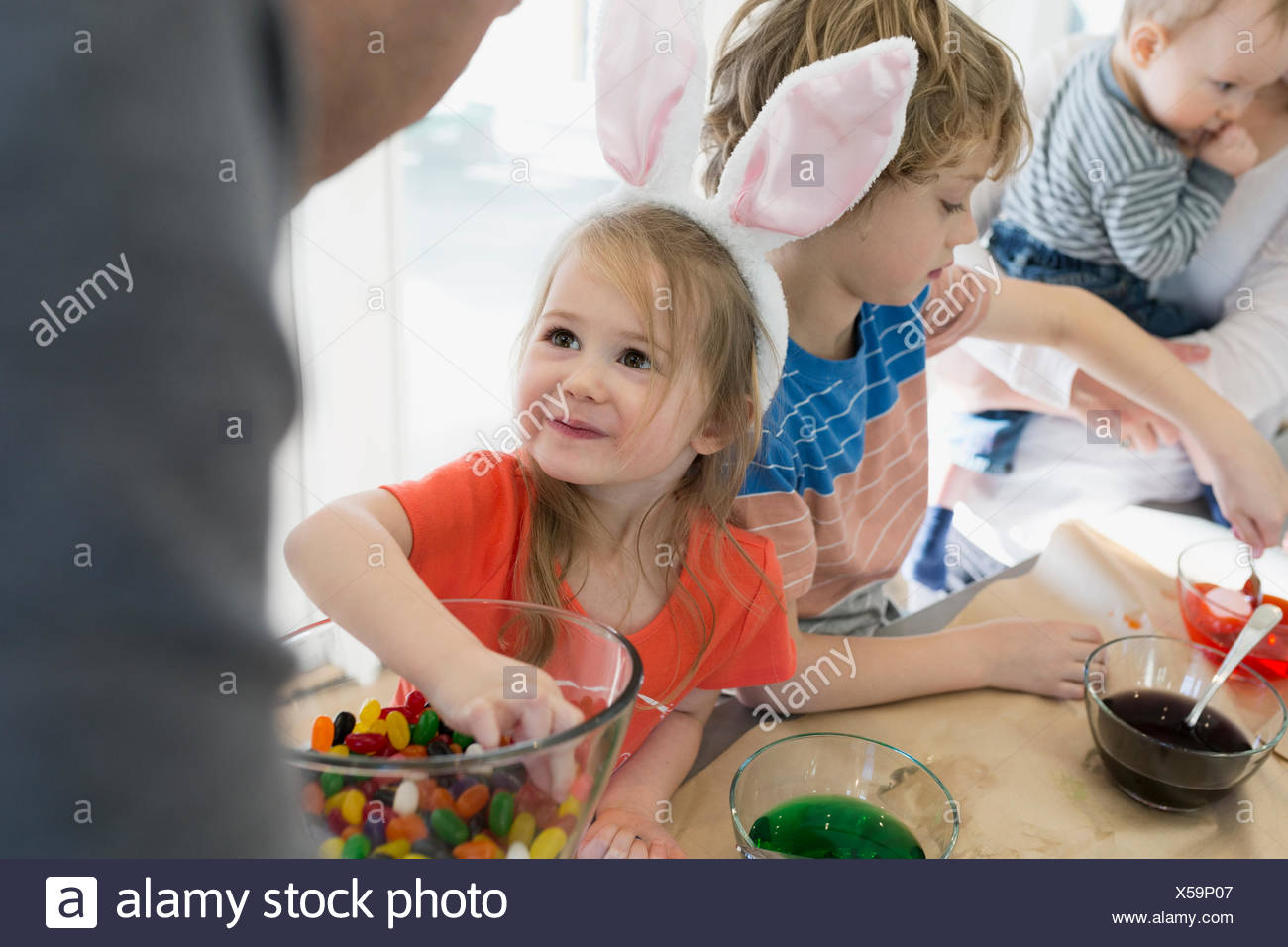 Cute daughter in bunny ears smiling up father - Stock Image