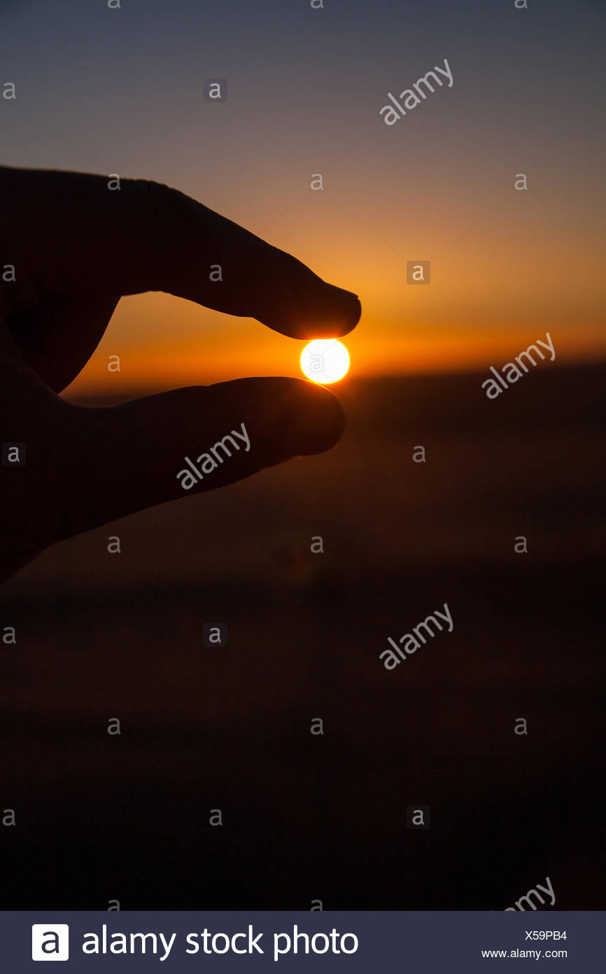 Silhouette of Hand Gripping the Sun - Stock Image