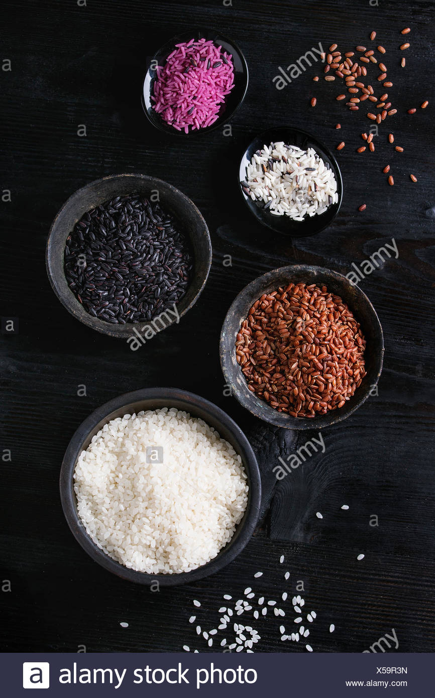 Variety assortment of raw uncooked colorful rice white, black, brown, pink in black bowls over burnt wooden background. Top view with space - Stock Image