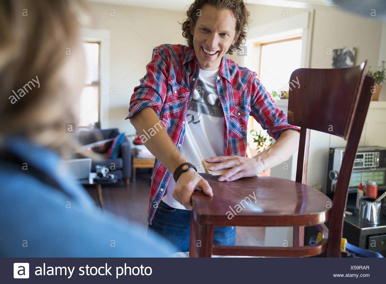 Couple refinishing chair - Stock Image