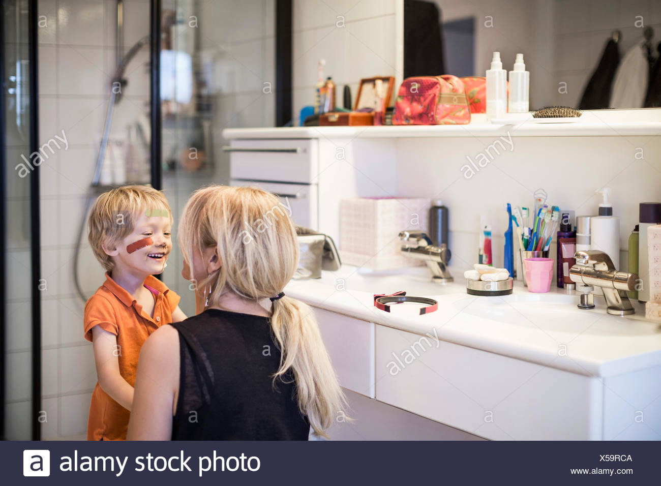 Woman looking at son's injured face in bathroom - Stock Image