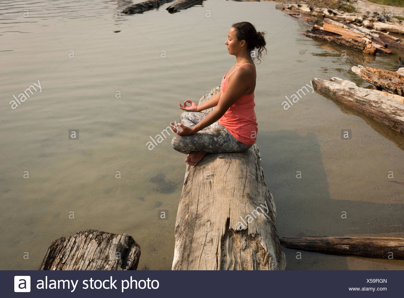 Fit woman sitting in meditating posture on a fallen tree trunk - Stock Image