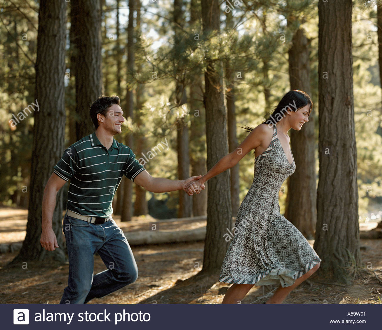 A couple running through the woods - Stock Image