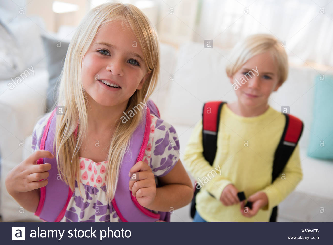 Boy (4-5) and girl (6-7) with backpacks, looking at camera - Stock Image