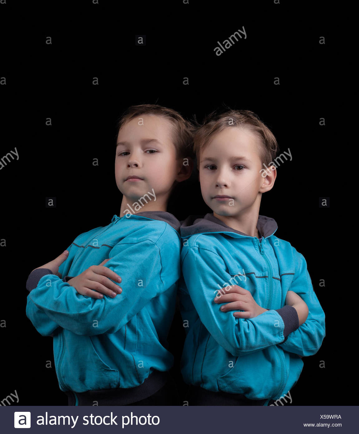 Portrait of adorable twin boys isolated on black