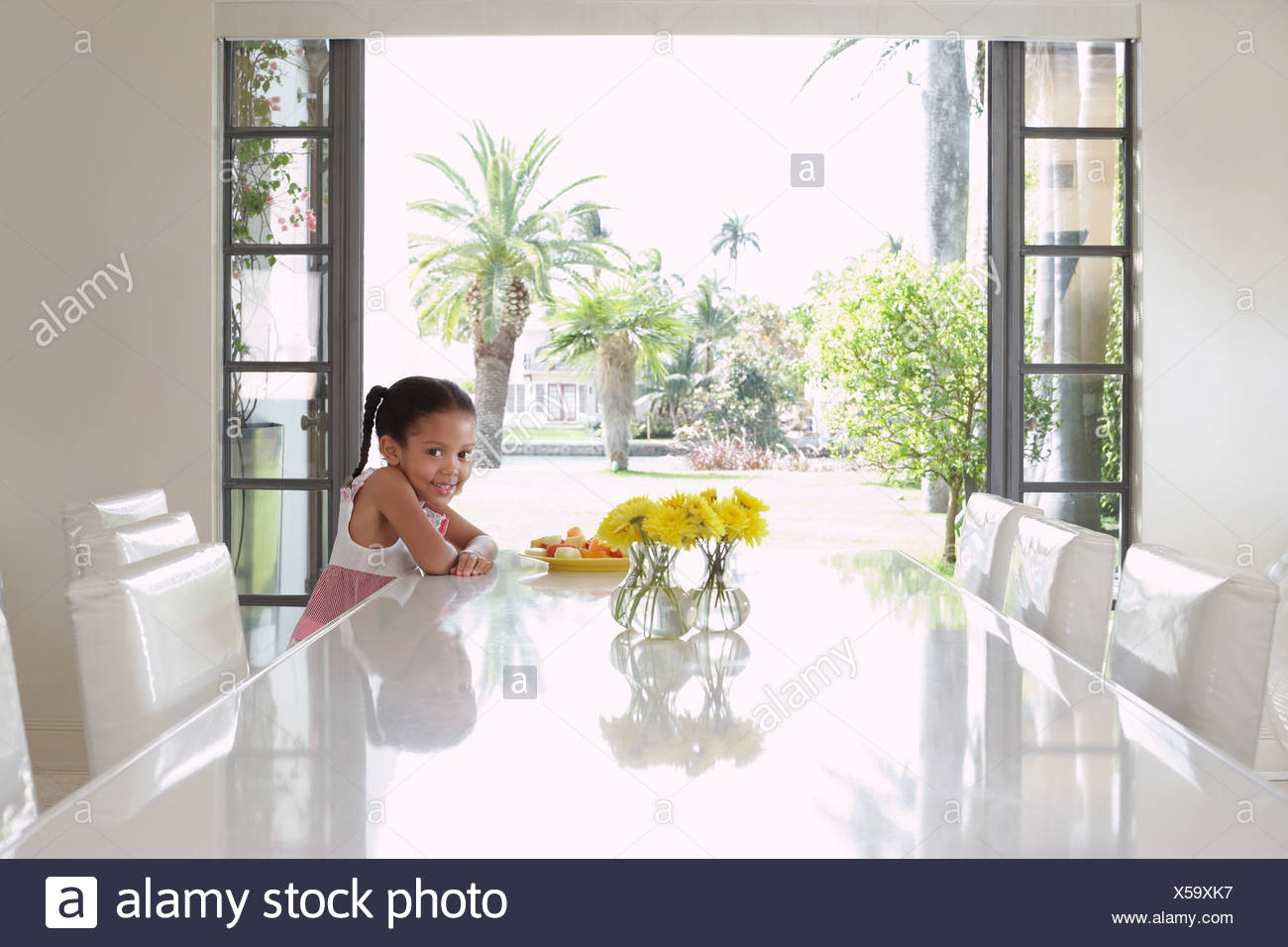 Girl (5-6 years) sitting at dining table - Stock Image