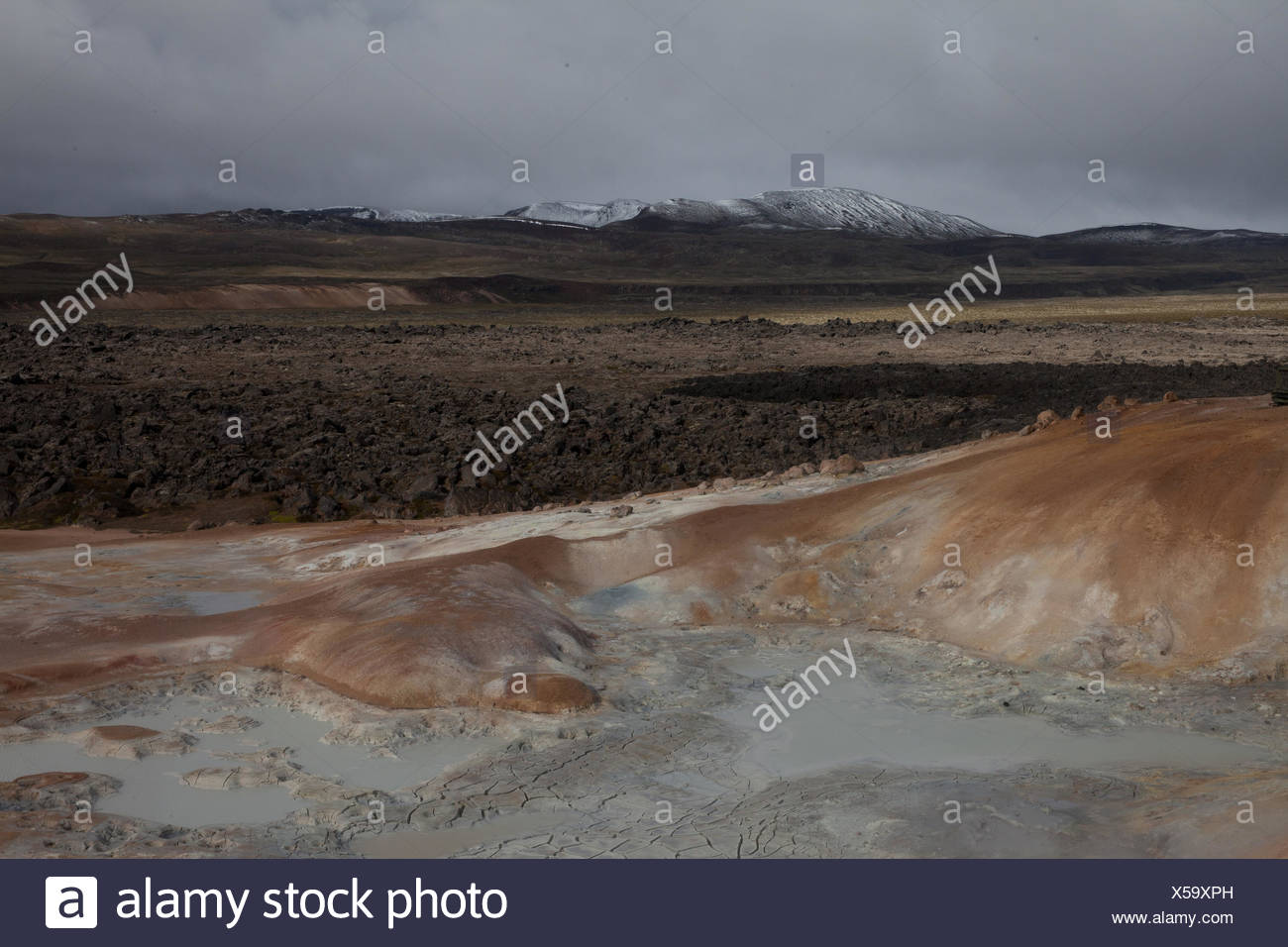 Cooled Volcanic Lava Against Arid Landscape - Stock Image