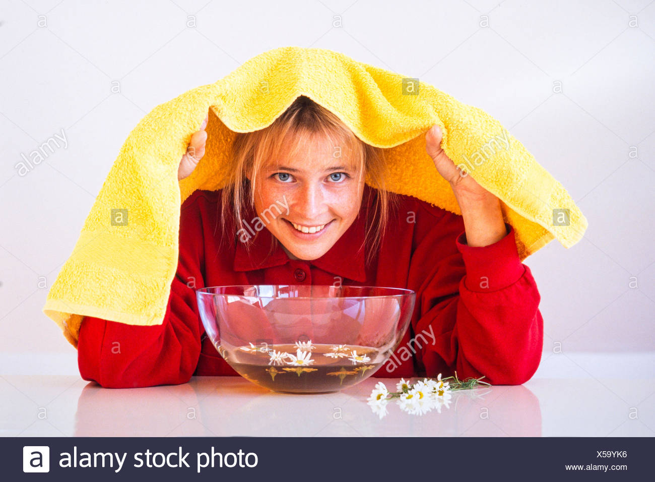 Woman while inhaling over a steam bath close camomile blossoms - Stock Image