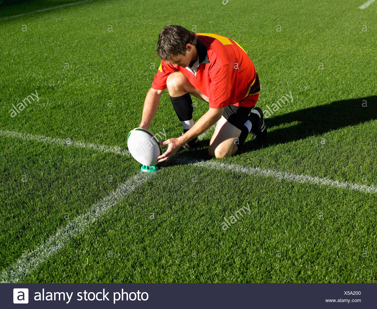 Rugby player placing ball - Stock Image