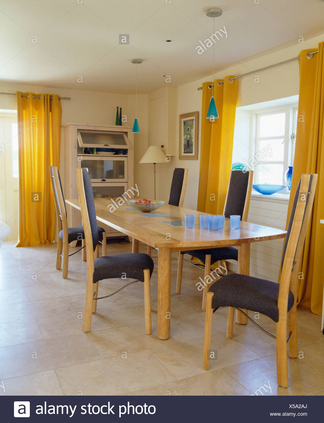 Yellow Curtains And Limestone Flooring In Modern Dining Room With Tall Back Chairs At Simple Pale Wood Table Stock Photo Alamy