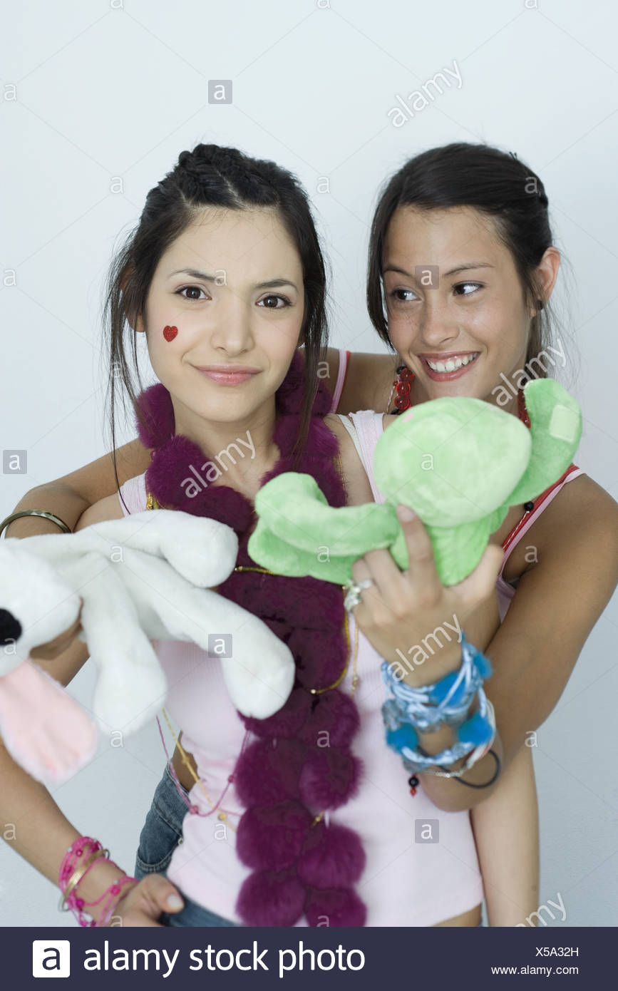 Two young female friends, one standing behind the other, holding out stuffed toys, portrait - Stock Image