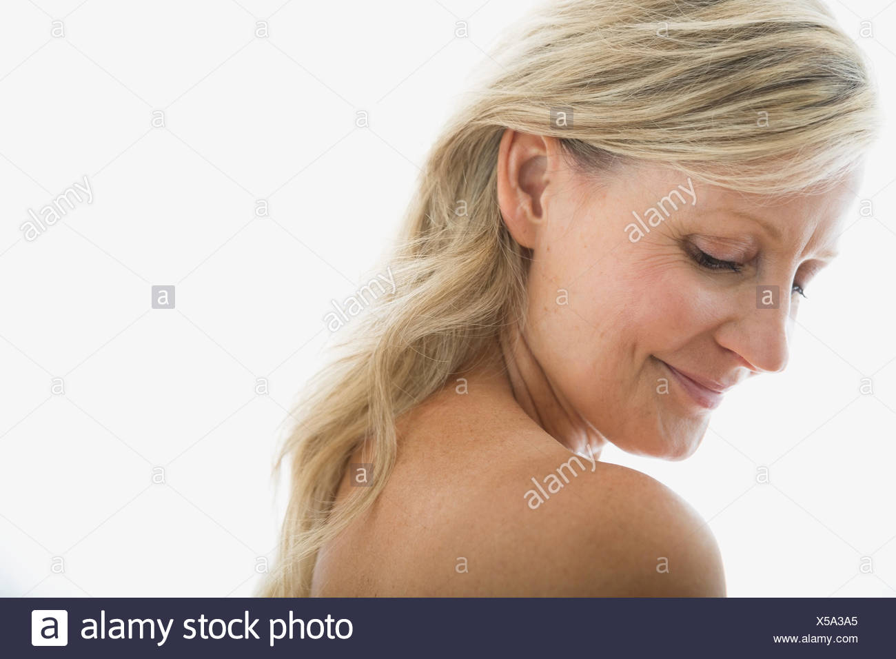 Blonde woman looking down at bare shoulder - Stock Image