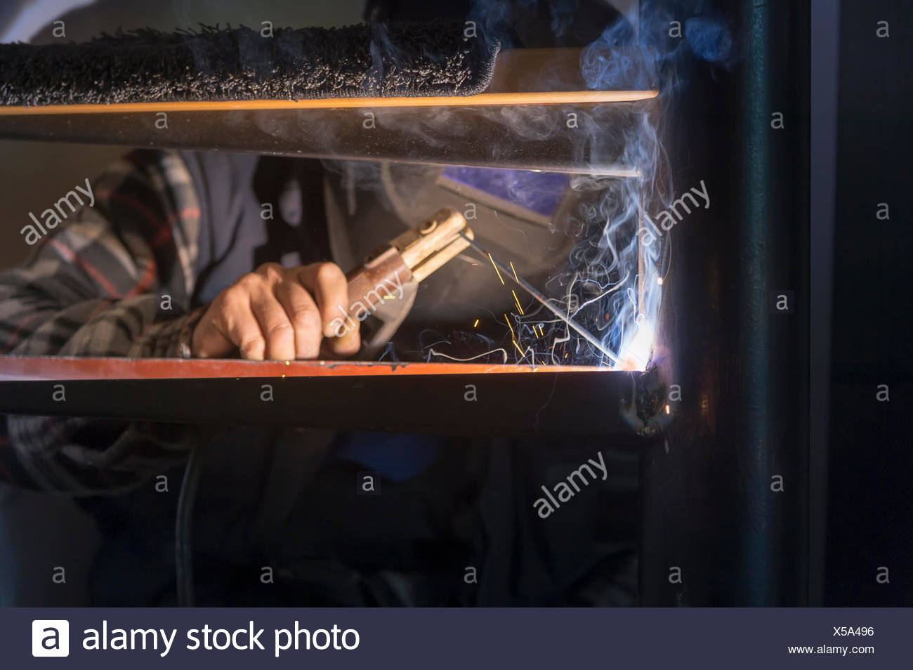 Man working on spiral staircase with electric torch - Stock Image