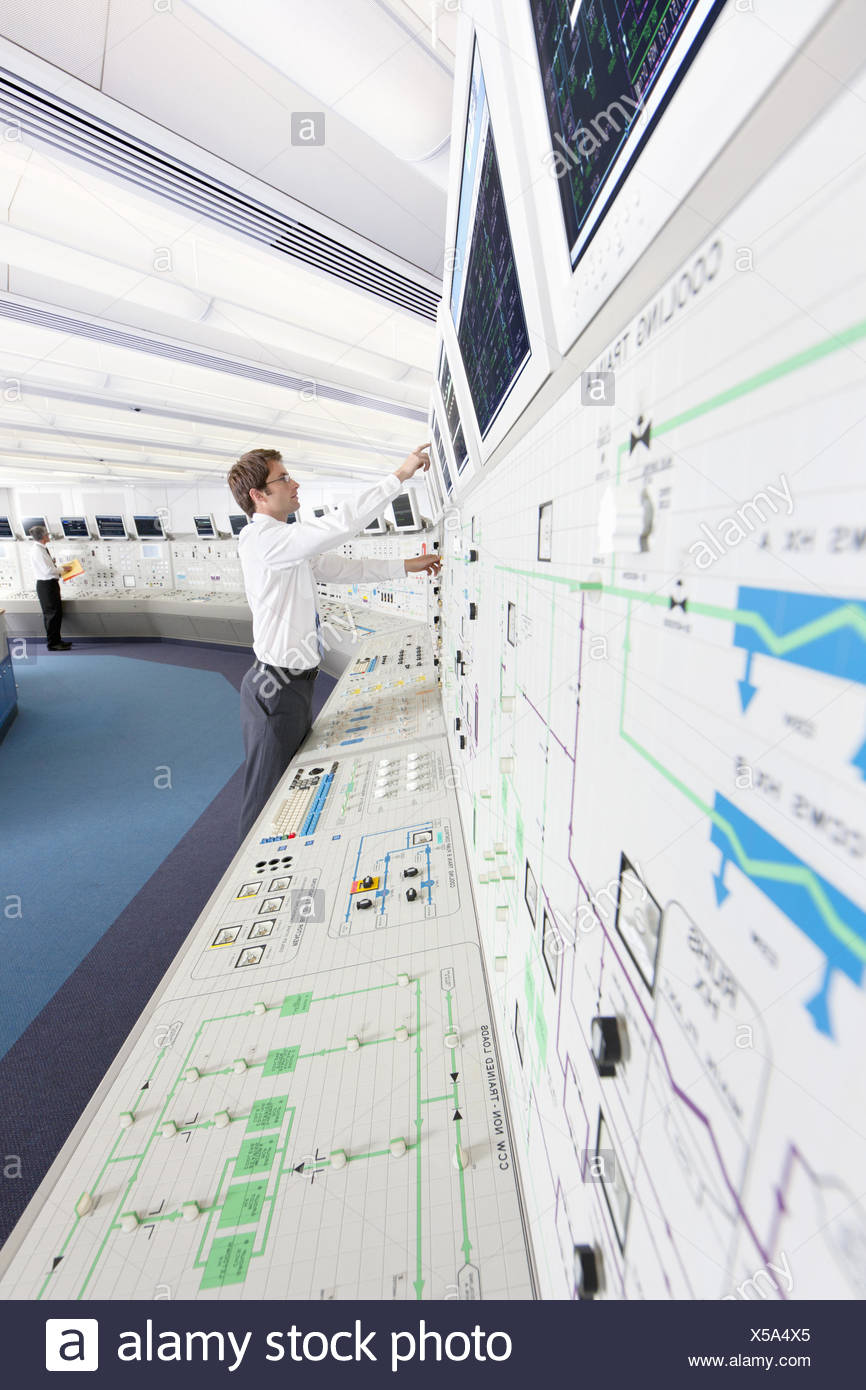 Engineer pointing to computer monitor in control room of nuclear power station - Stock Image