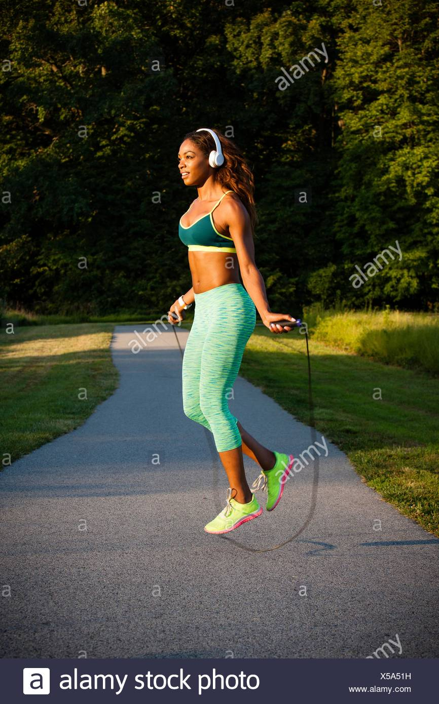 Young woman training with skipping rope on path - Stock Image