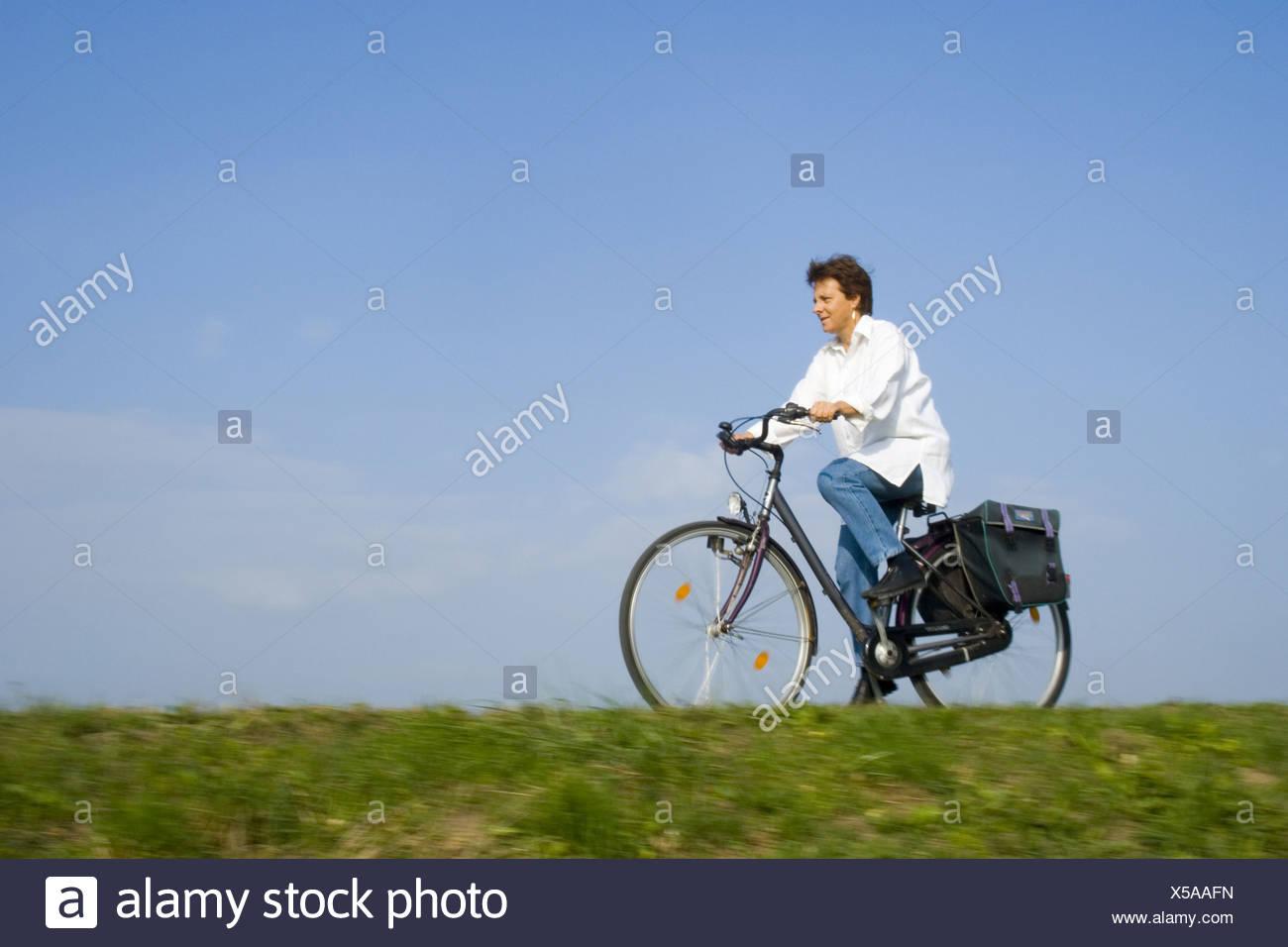 elderly woman on a bike - Stock Image