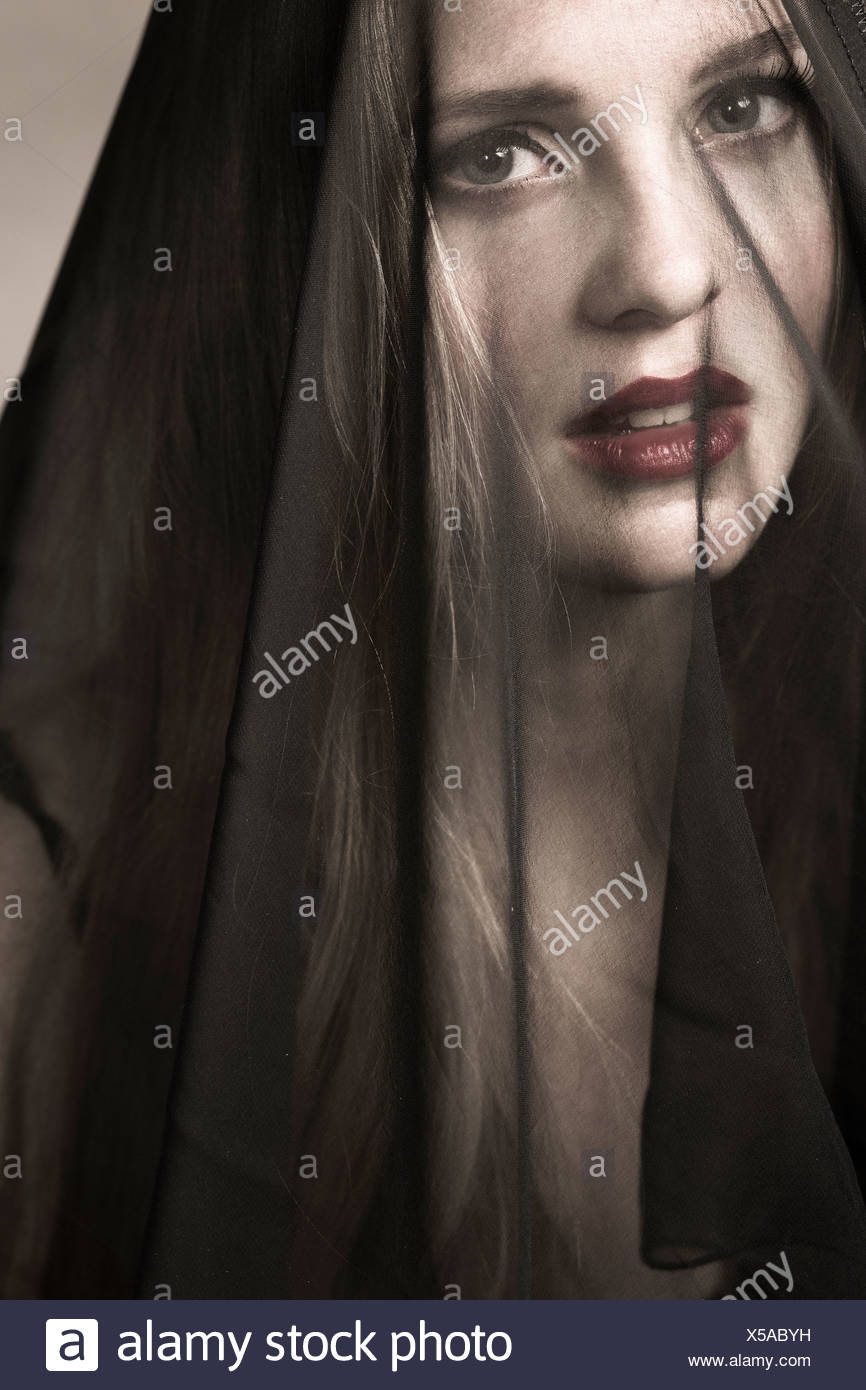 Portrait of young woman wearing mourning veil - Stock Image
