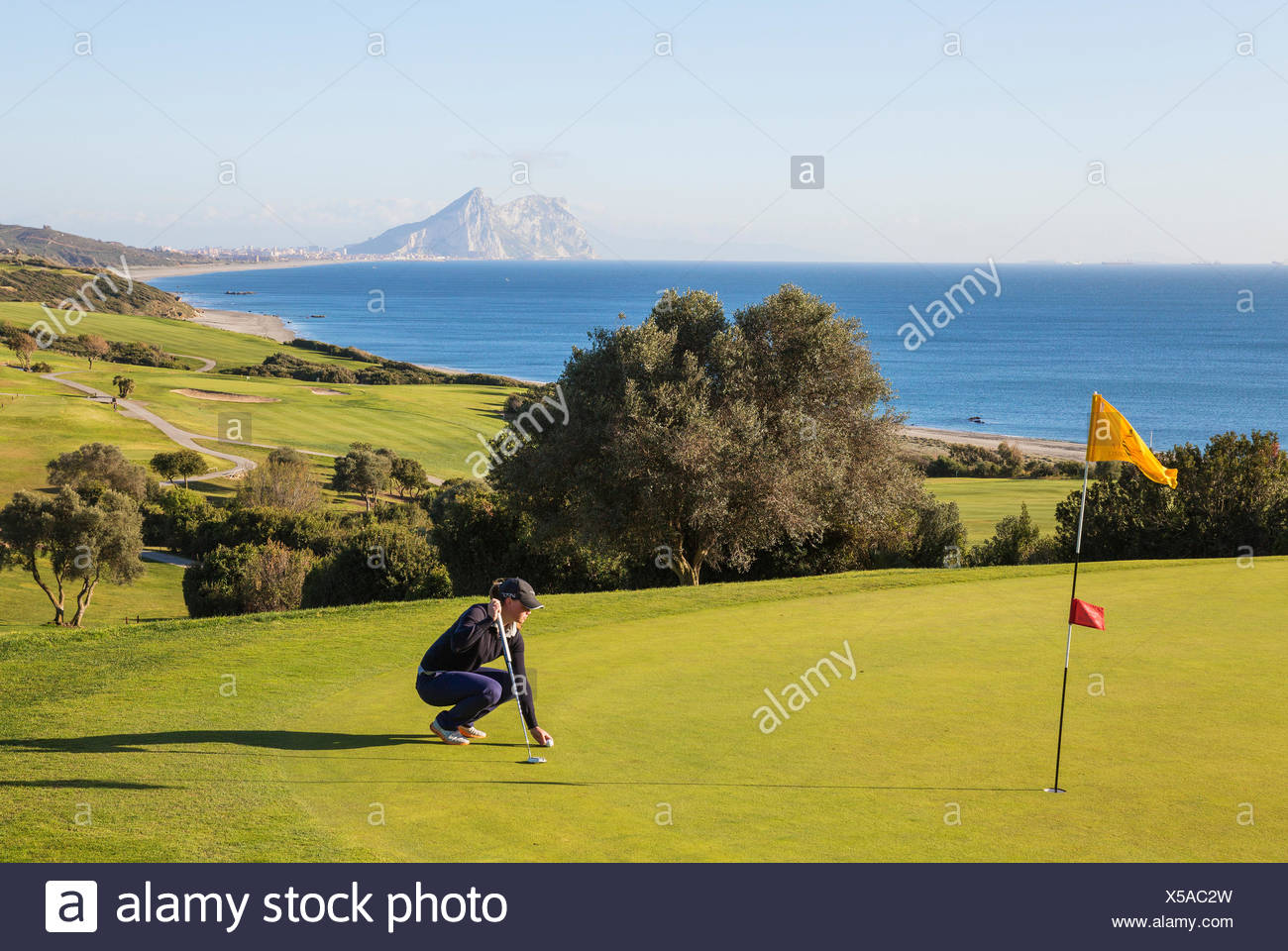 Golfer on putting green, La Alcaidesa Golf Resort with Mediterranean Sea and Rock of Gibraltar, Cádiz, Andalusia, Spain - Stock Image