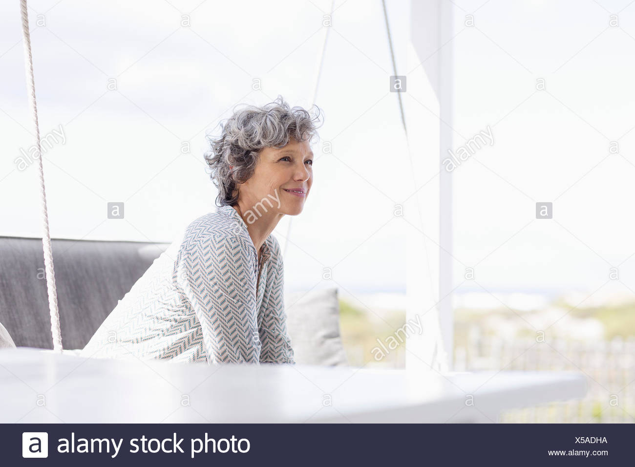 Woman sitting on a swing and day dreaming - Stock Image
