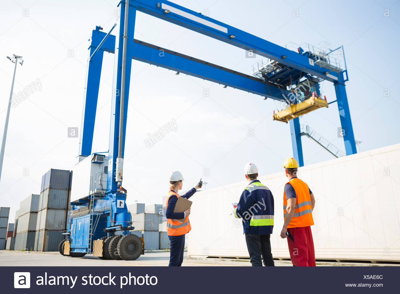 Workers discussing against large crane loading container at shipping yard - Stock Image