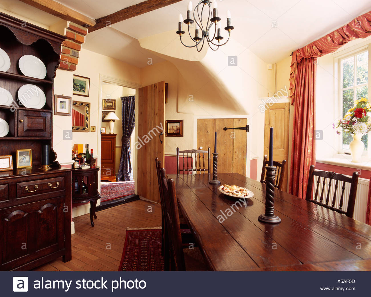 Antique rectangular wooden table and chairs in country diningroom with wooden floor - Stock Image
