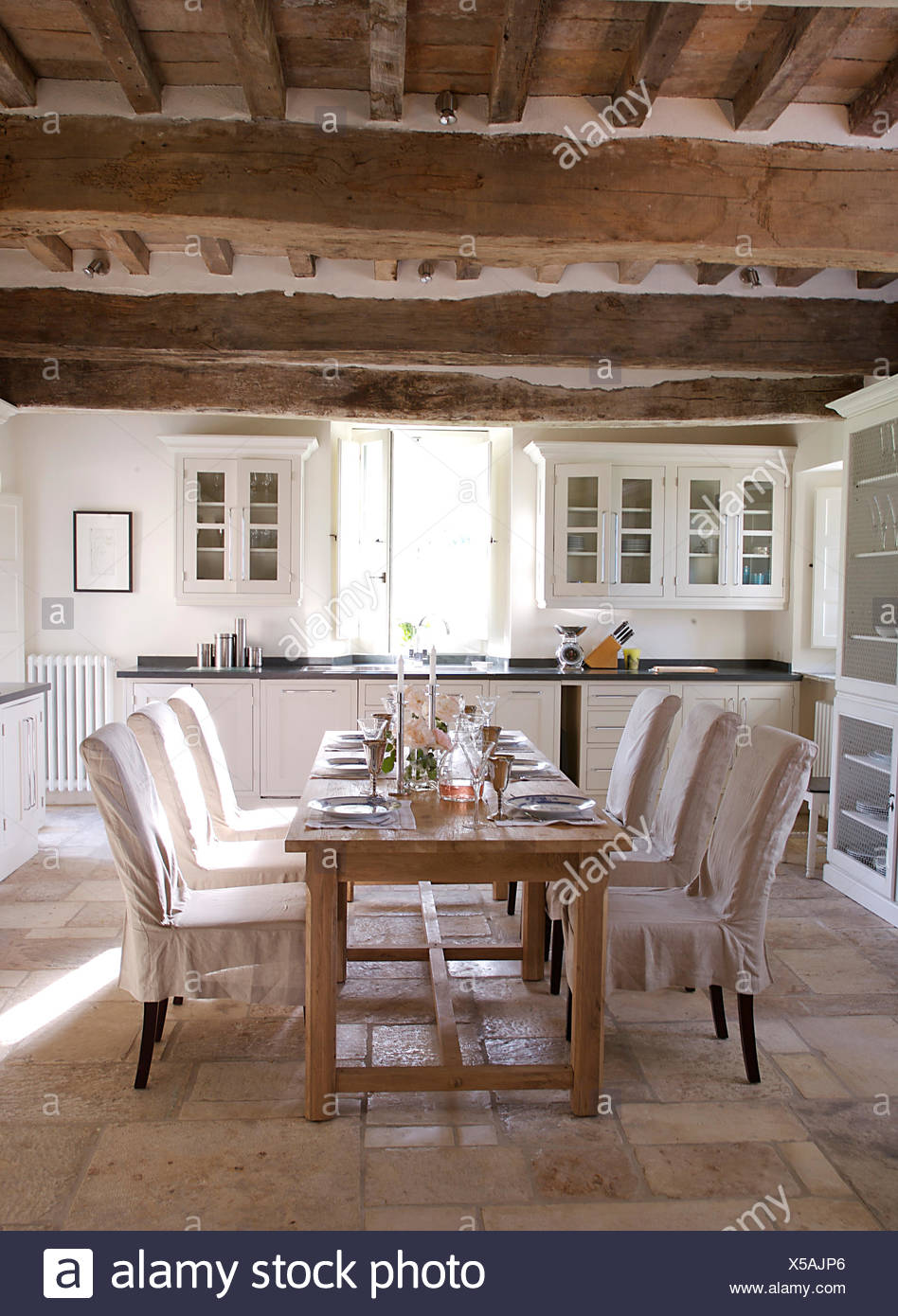 White Loose Covers On Chairs At Simple Wooden Table Set For Lunch In Italian Country Dining Room
