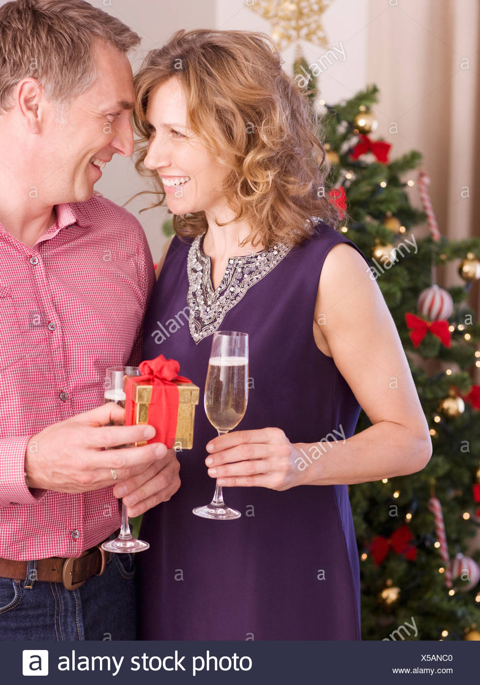 Couple holding champagne and gift near Christmas tree Stock Photo