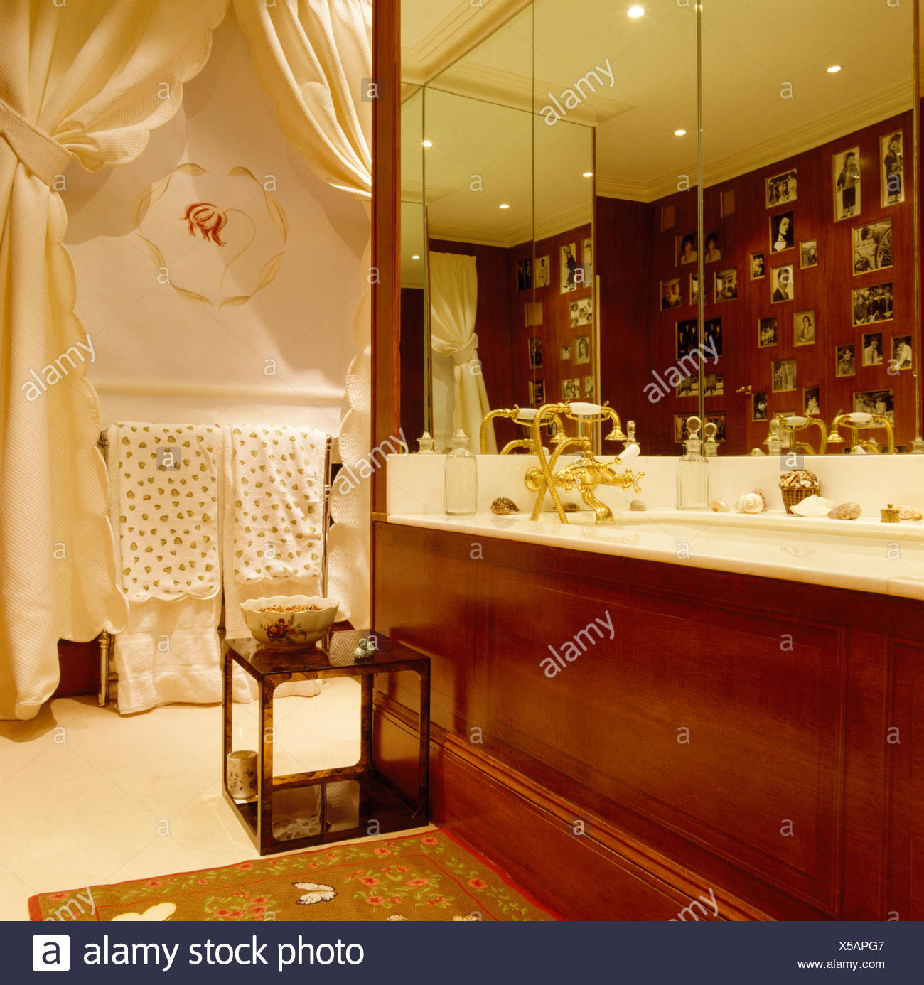 Mirrored wall above bath with polished wood panel in bathroom with small table and window with cream drapes - Stock Image