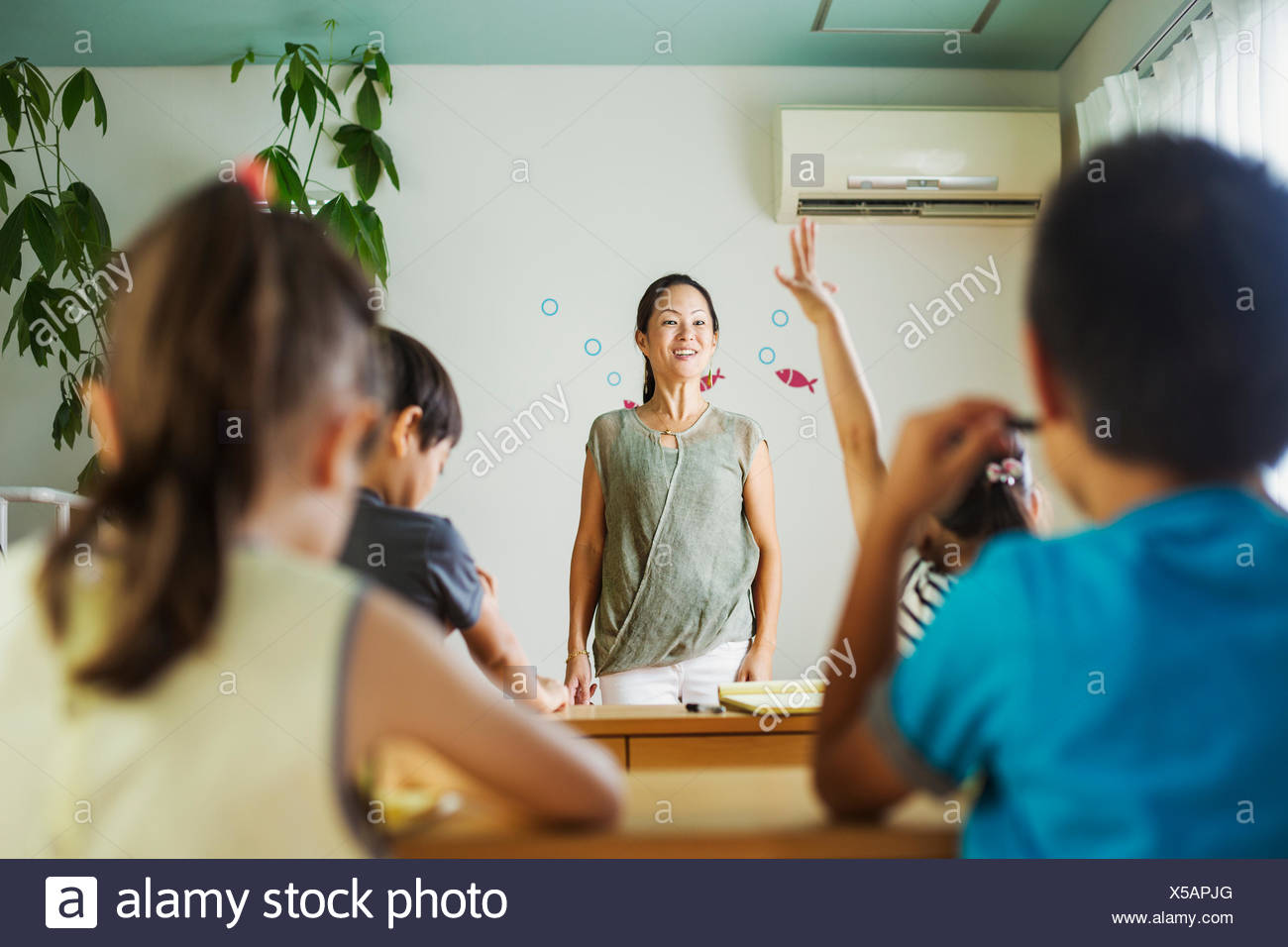 A group of children in a classroom, one with her hand up ready to answer a question. - Stock Image