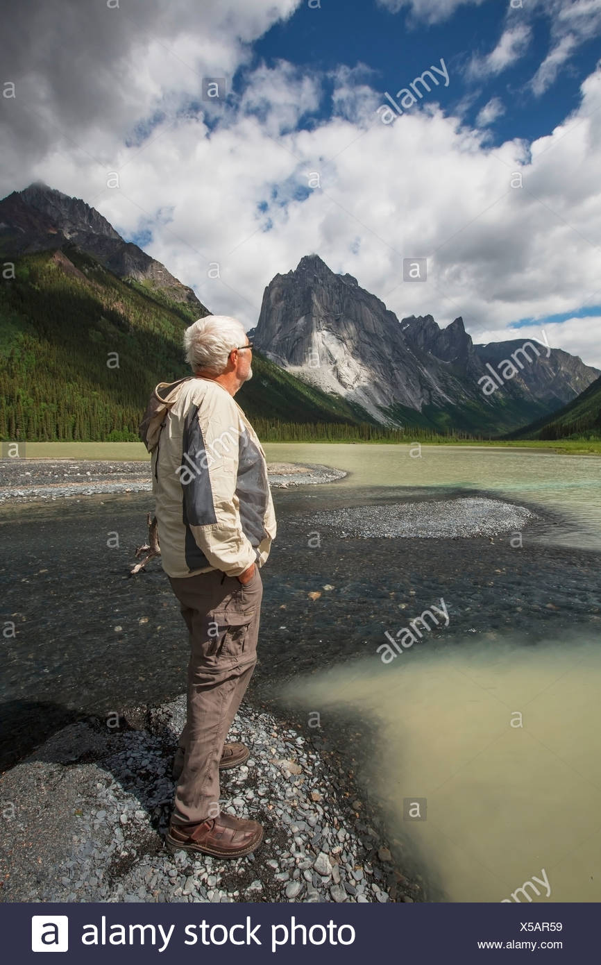 Man Stands On The Shores Of Glacier Lake; Northwest Territories, Canada - Stock Image