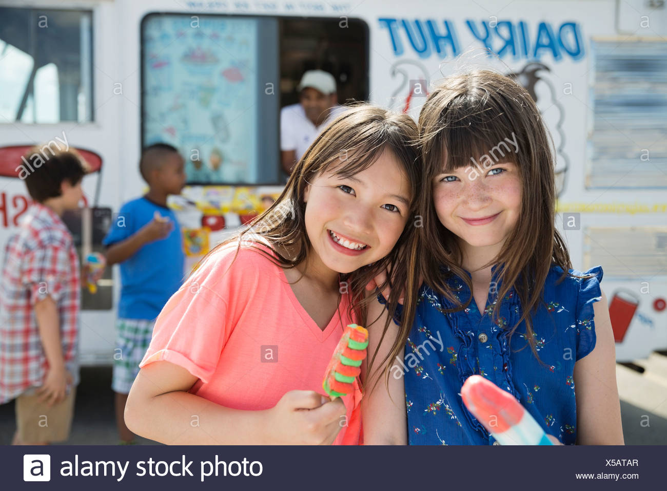 Portrait of cute girls holding popsicles - Stock Image