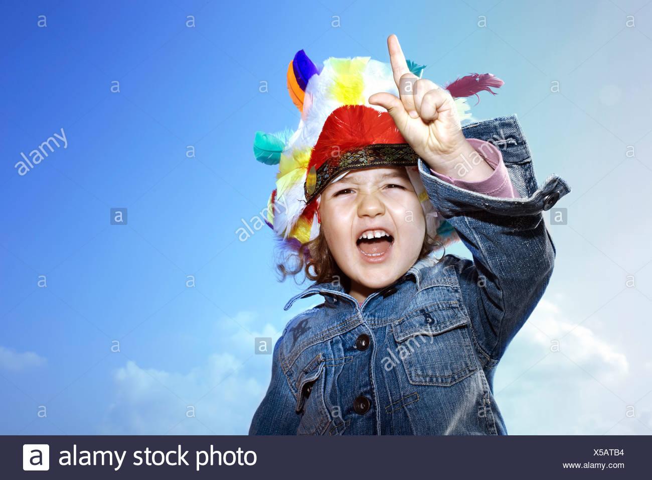 Toddler girl wearing Indian headdress - Stock Image