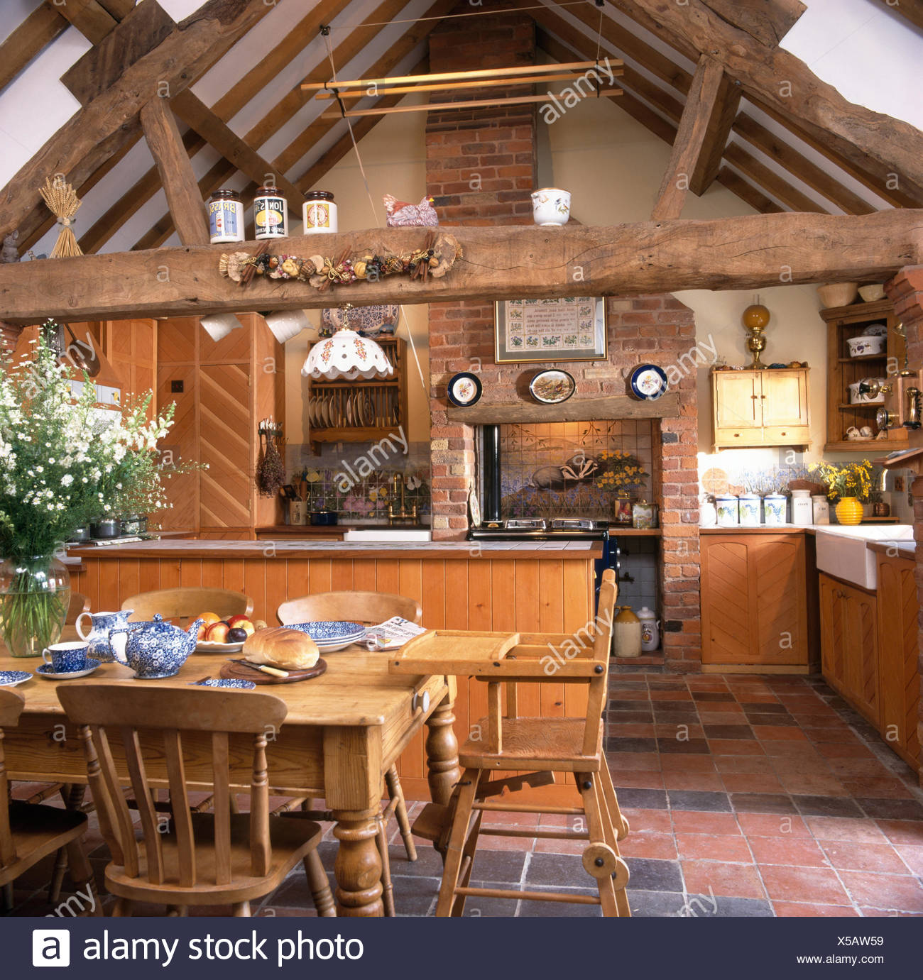 Wooden chairs and childu0027s high chair at pine table in barn conversion kitchen with rustic wooden beams & Wooden chairs and childu0027s high chair at pine table in barn ...