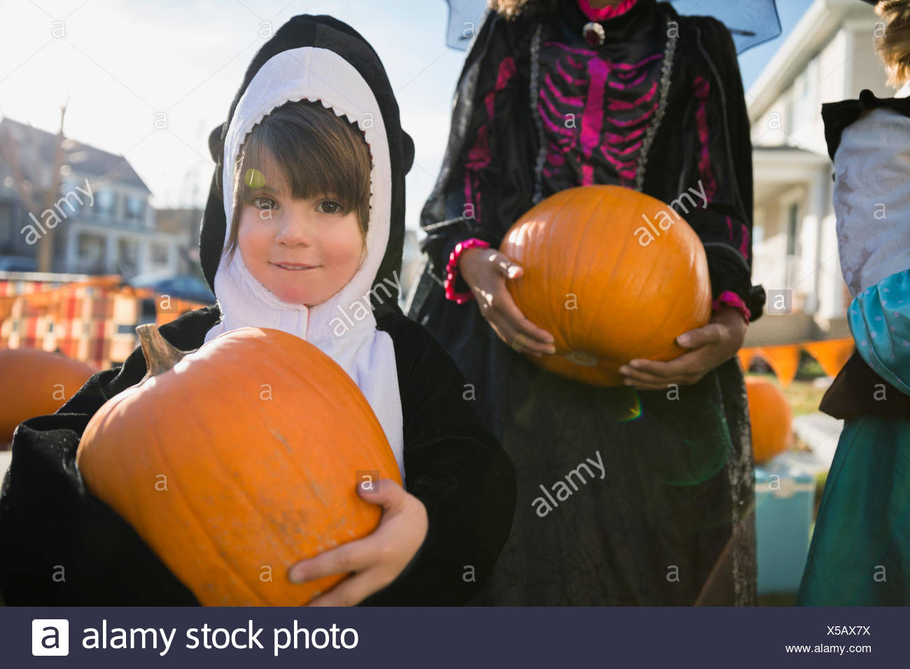 portrait boy in whale halloween costume holding pumpkin stock photo