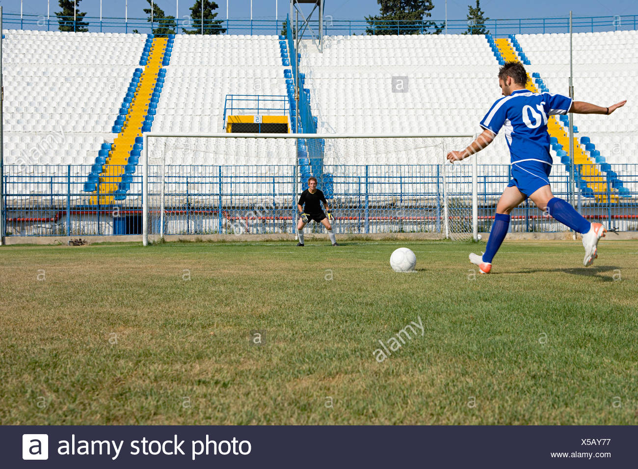 Footballer kicking football - Stock Image