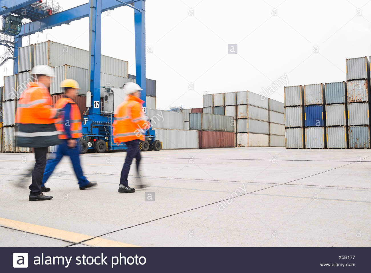 Full-length rear view of workers walking in shipping yard - Stock Image