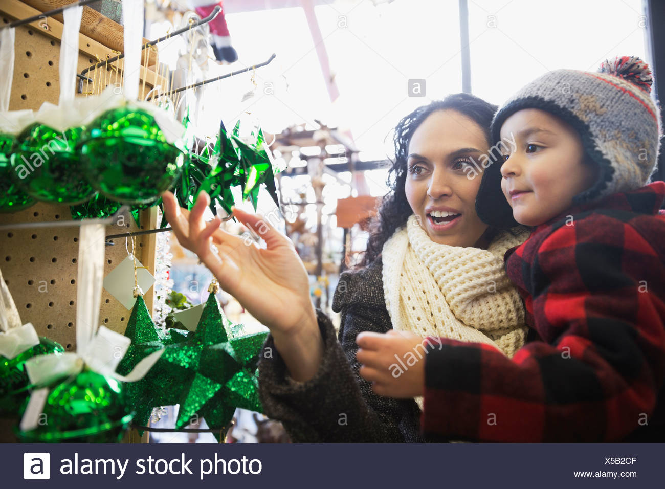 Mother and son shopping for Christmas ornaments in store - Stock Image