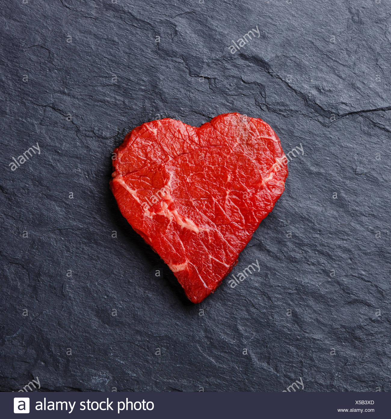 Heart shape Raw fresh meat on dark stone slate background - Stock Image