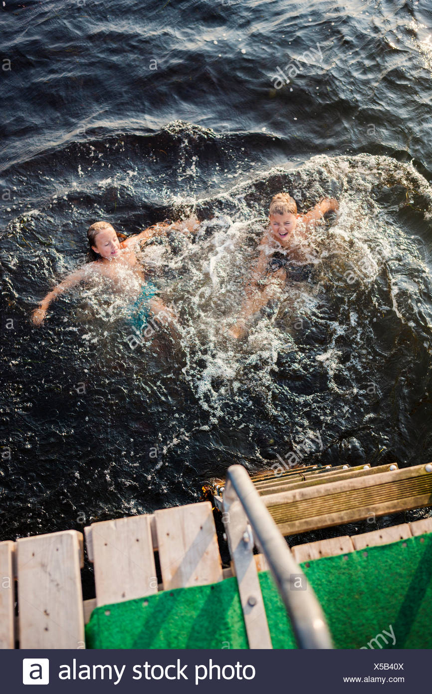 Sweden, Oland, Gronhogen, Brother (10-11) and sister (6-7) swimming - Stock Image
