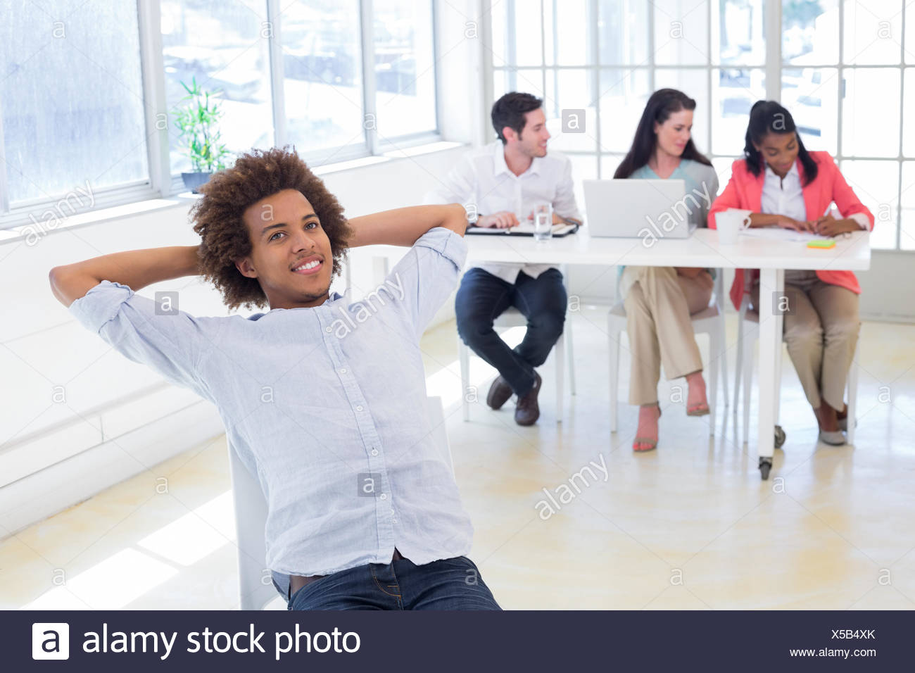 Businessman relaxing with coworkers behind him - Stock Image