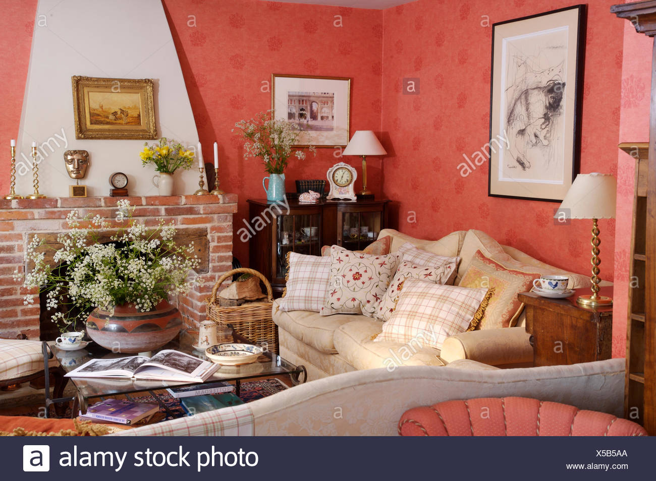 Cream Sofa Piled With Cushions In A Deep Pink Cottage Sitting Room With  Bowl Of Cow
