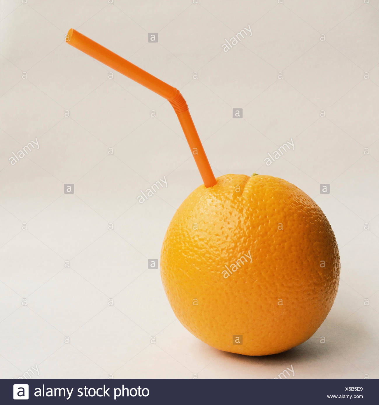 Orange with straw - Stock Image