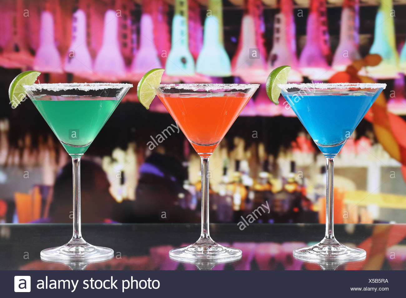 Bunte Cocktails in Martini Gläsern in einer Bar - Stock Image