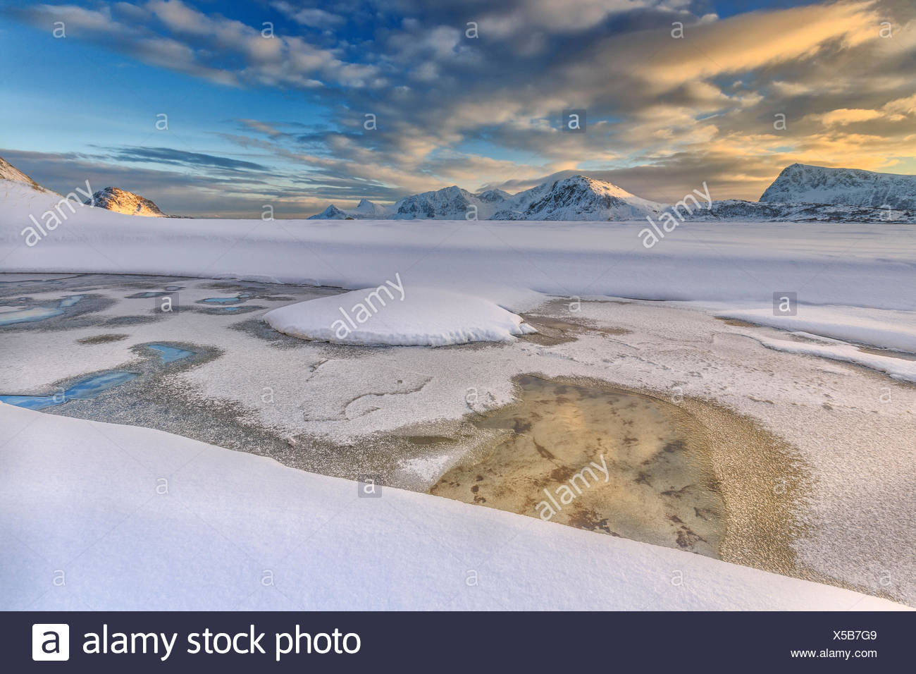 The golden sunrise reflected in a pool of the clear sea where the snow is almost melted. Haukland Lofoten Islands Norway Europe Stock Photo
