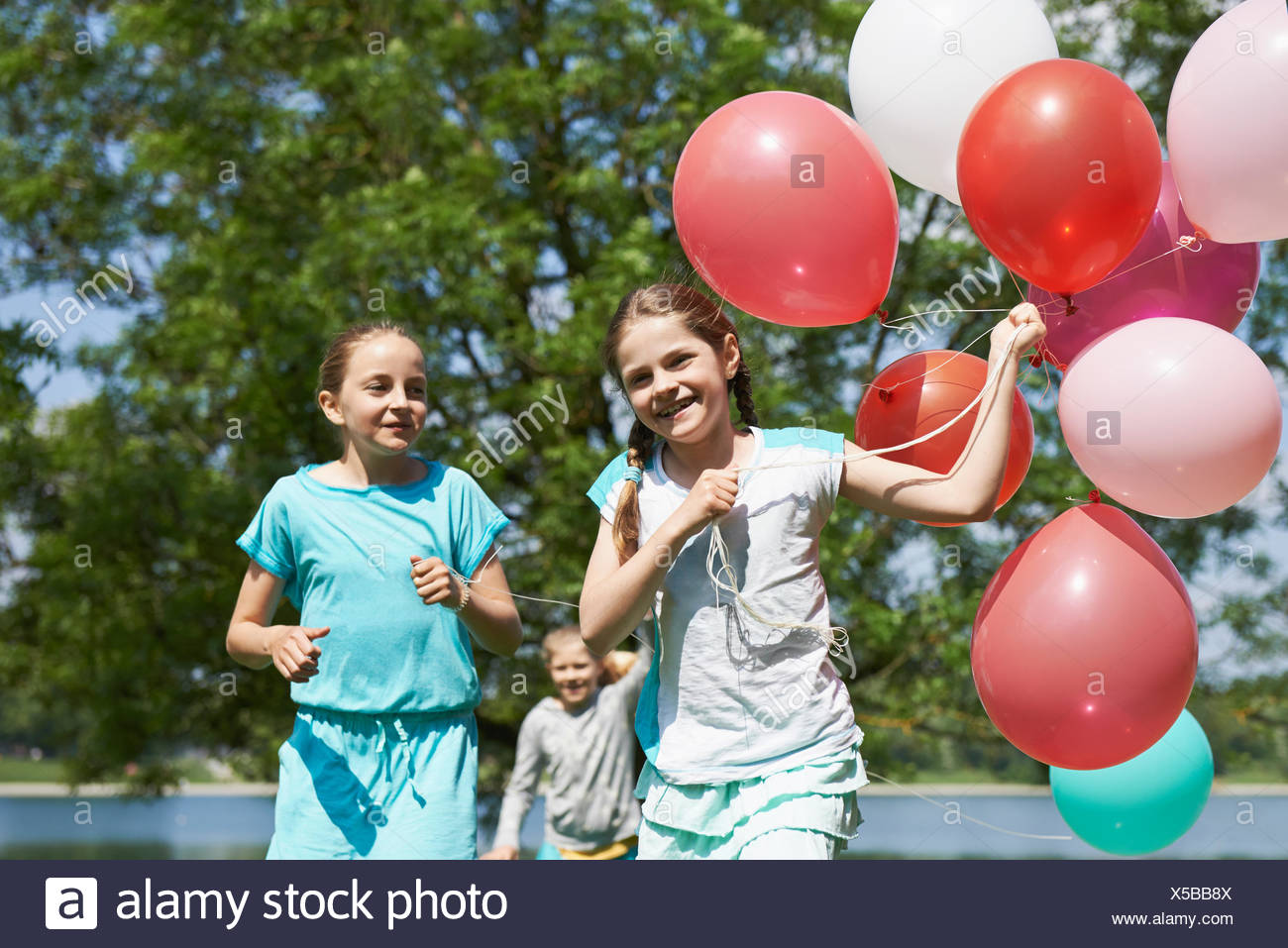 Girls running in park with balloons, Lake Karlsfeld, Munich, Bavaria, Germany - Stock Image