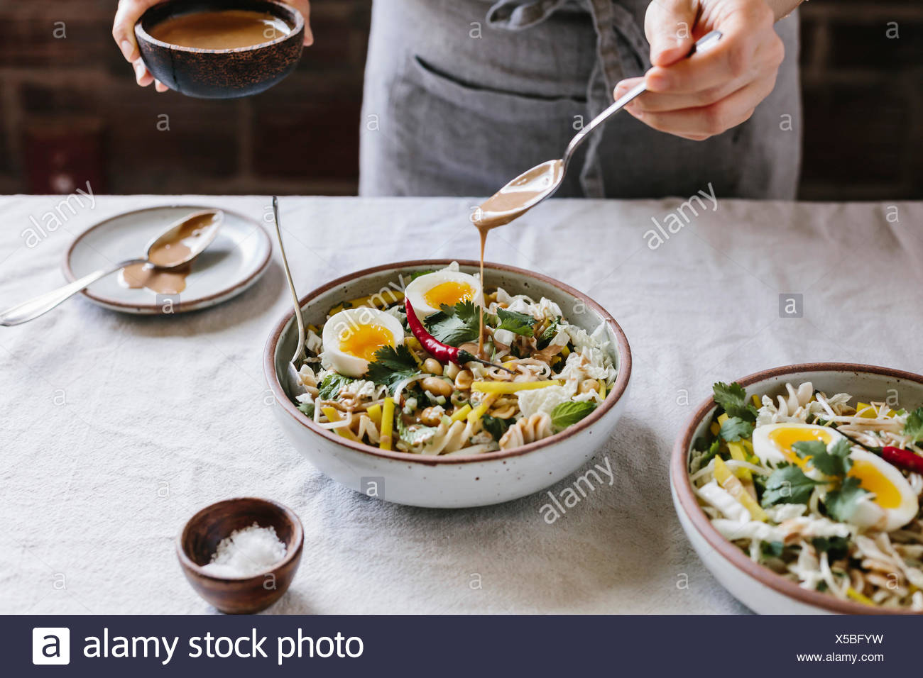 A woman is drizzling a veggie bowl with warm peanut dressing photographed from the front view. - Stock Image