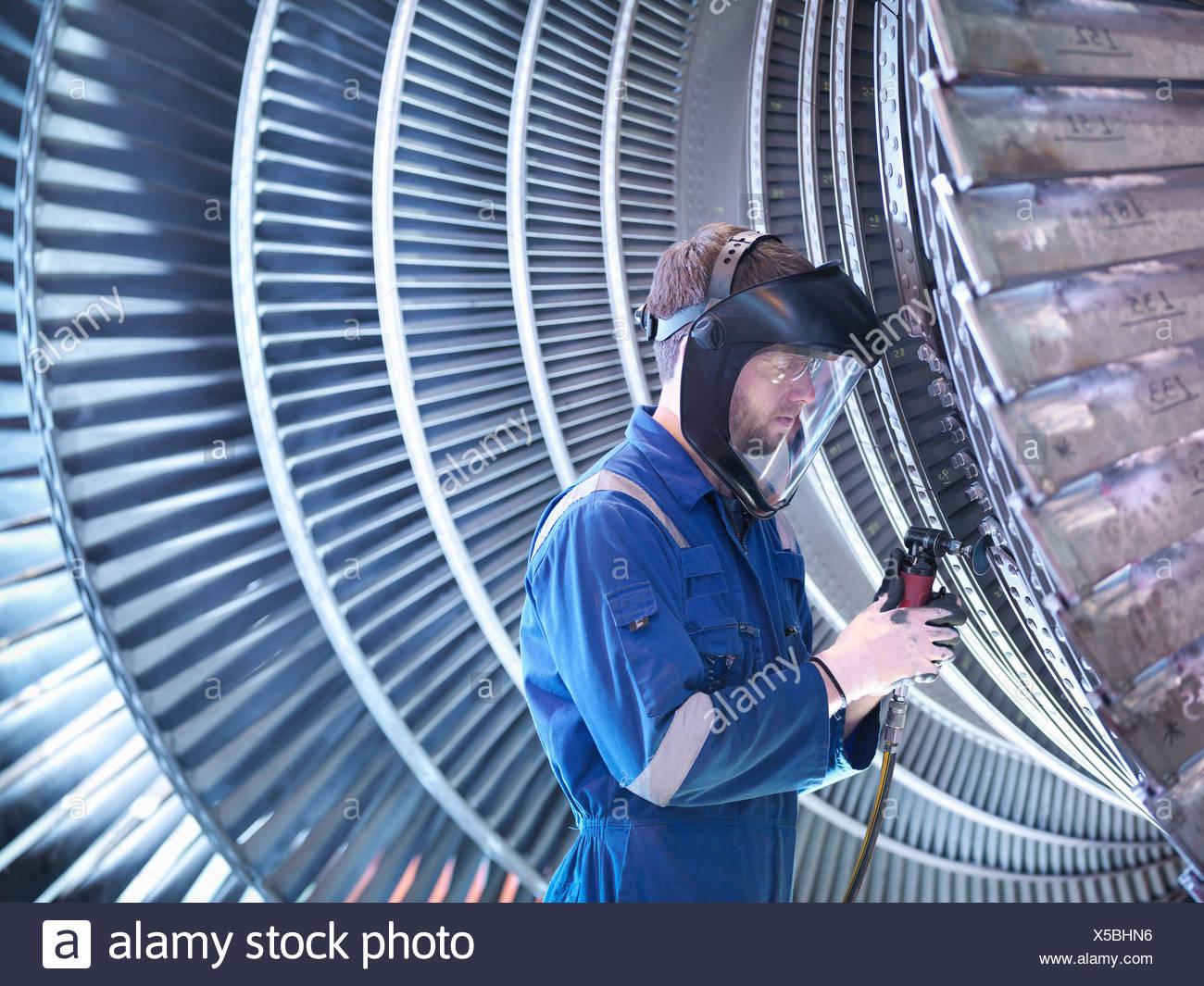 Engineer repairing steam turbine blade with grinder in workshop - Stock Image