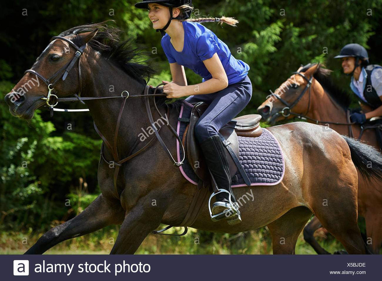 Side view of girl riding horse smiling - Stock Image